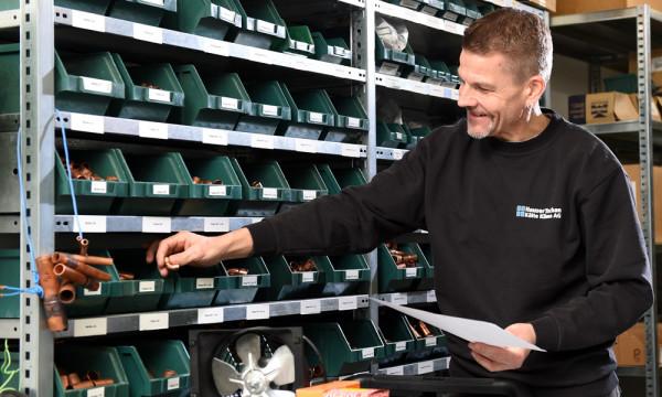 Foto: Mitarbeiter nimmt Ersatzteile aus dem gut sortierten Lager/Gestell.